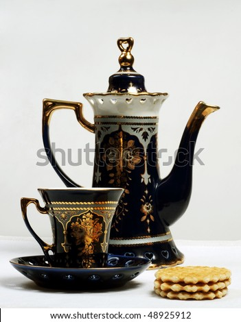 teapot, teacup and cookies on table - stock photo