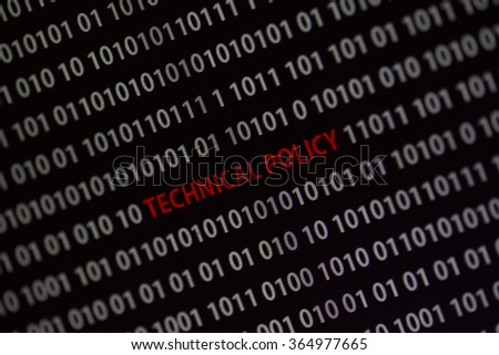 'Technical policy' text in the middle of the computer screen surrounded by numbers zero and one. Image is taken in a small angle.
