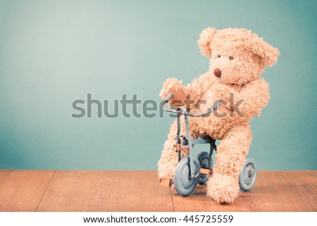 Teddy Bears is sitting on old retro toy bicycle in front mint green background. Vintage style filtered photo