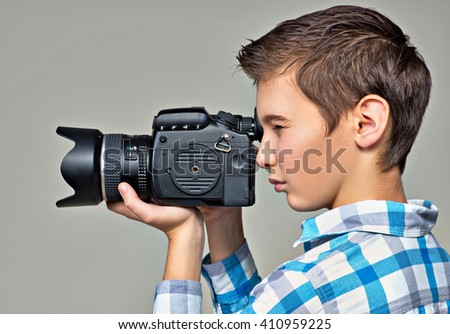 Teen boy  with dslr camera photographing. Boy with camera taking pictures. Profile portrait. - stock photo