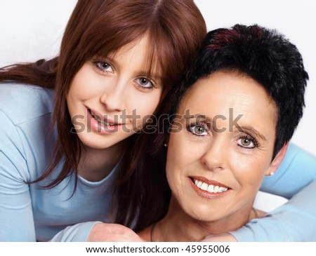 Teenage daughter embraces mature mother