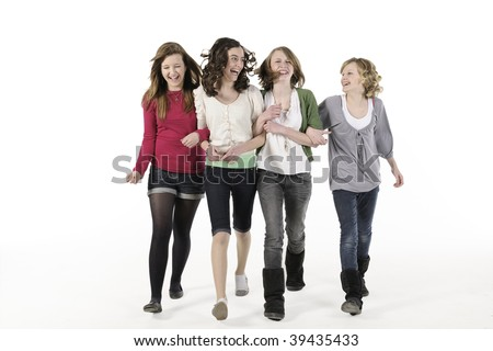 4 teenage girls linking arms walking towards camera smiling