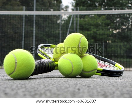 Tennis equipment on the court , Tennis balls and racket left on the court - stock photo