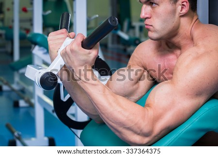Tense muscles of hands under load. Man doing exercise for biceps in the gym. Work on tell muscles on the simulator. Photos for sporting magazines, posters and websites.  - stock photo