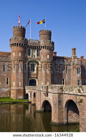 15th century English moated castle flying flags of Canada and the United Kingdom (union flag); reflection in the moat
