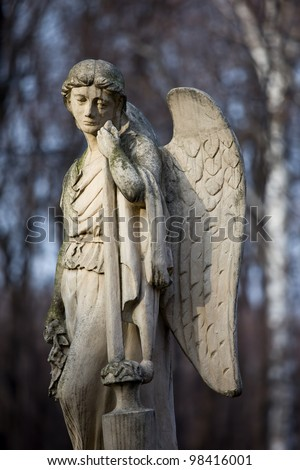 19th century statue of an angel with sad expression on face at Warsaw cemetery in Poland
