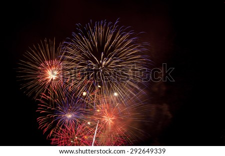 4th July fireworks explode in sky. Purple and orange burst. - stock photo