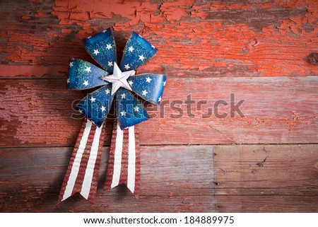 4th July patriotic badge in the form of a circular rosette with blue stars and a ribbon with the red and white stripes of the national flag on rustic wood - stock photo
