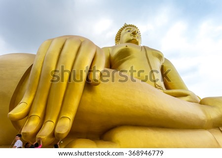 28th september 2015 at Wat Muang in Ang Thong Province Thailand : unidentified asian people pray and wish by the finger tip of gigantic outdoor buddha image