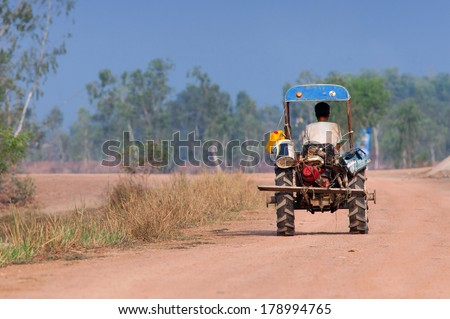 Thai farmer is driving his tractor to home. Thailand  - stock photo