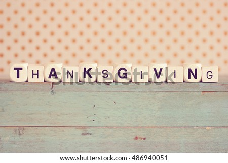 """THANKSGIVING"" printed on dice against rustic wood background with polka dots"