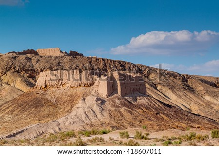 The ancient fortress of Ayaz-Kala in the Kyzylkum desert in Uzbekistan. Walls of clay. Fortress on a background of blue sky and white clouds at sunset.