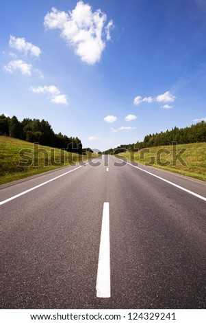 the asphalted road to summertime of year. at the edges of the road on a height the grass and trees (wood) grows - stock photo