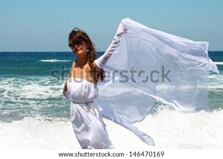 The beautiful girl at the sea in white developing clothes on a sea-breeze - stock photo