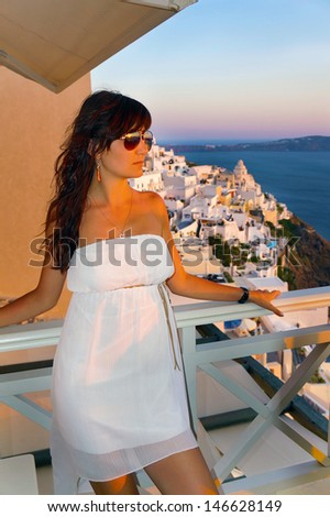 The beautiful girl in a white dress against an island Santorini decline - stock photo