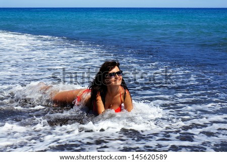 The beautiful girl in the sea on a black beach of island Santorini. Greece - stock photo