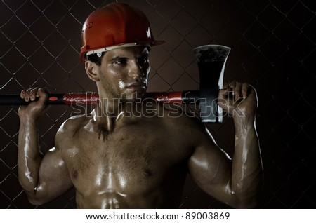 the beauty muscular worker  chopper  man, in  safety helmet  with big  heavy ax  in hands, tired  appearance , on netting fence background - stock photo