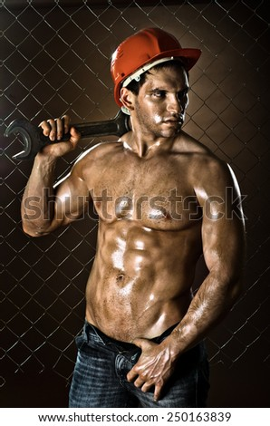 the beauty muscular worker  man, in  safety helmet  with big wrench  in hands, on netting fence background - stock photo
