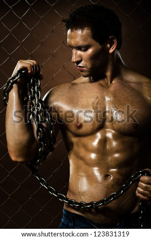 the beauty muscular worker  man,  with big  chain in hands, on netting fence background - stock photo