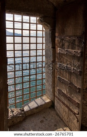 The big window aperture closed by a lattice in a fortress Shillon on coast of lake Leman