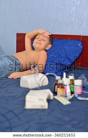 The boy is sick. He lies on the bed and holding his head - stock photo