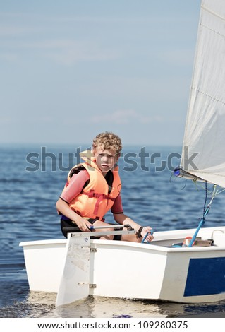 The boy operates the yacht - stock photo