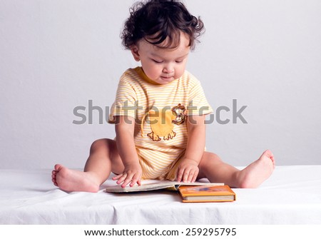 The child considers the children's book with pictures. - stock photo