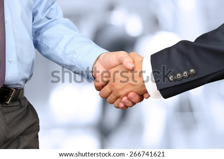 The Close-up image of a firm handshake between two colleagues in office. - stock photo