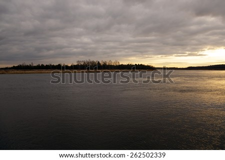 the dawn sun over the lake in the autumn. Overcast. - stock photo