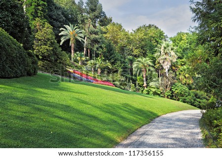 The flowerbeds, green grassy lawn and comfortable path in an exotic park. Lake Como, Villa Carlotta - stock photo