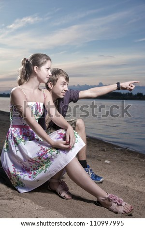 The girl and the young man sit on coast