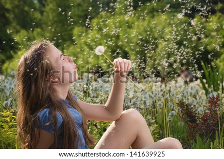The girl blows on a dandelion - stock photo