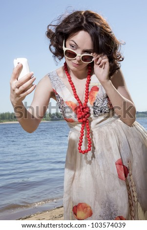 The girl in sun glasses looks at phone - stock photo