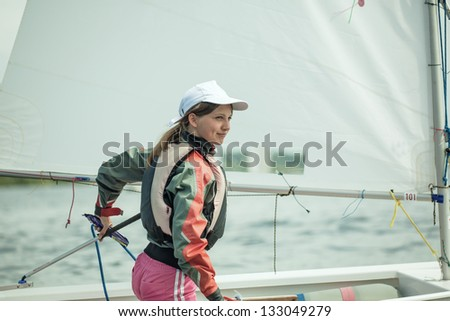 The girl operates the yacht the Optimist - stock photo