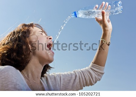 The girl pours water from a bottle - stock photo