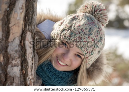 The girl smiles looking out because of a tree trunk - stock photo