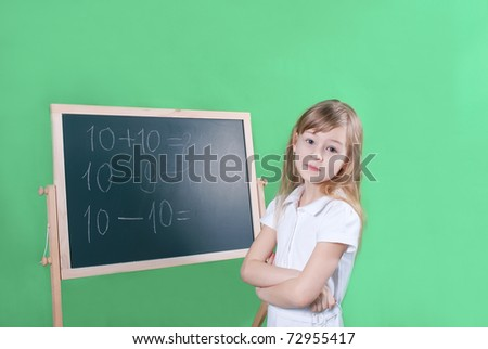 the girl solves examples on a board. - stock photo