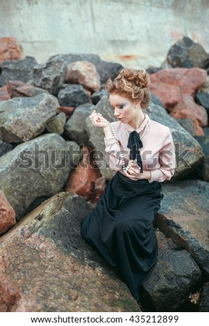 The girl with pearls near the sea. Elegant woman is playing with her pearl necklace on the stone coast. She is wearing pink blouse.