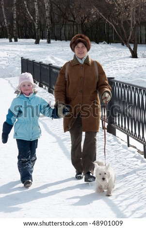 The grandmother with the granddaughter and dog on walk - stock photo