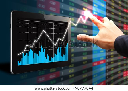 The hand point to high graph on Tablet computer - stock photo