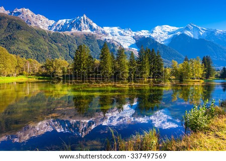 The lake reflected the snow-capped Alps and evergreen spruce. Early autumn in Chamonix, France