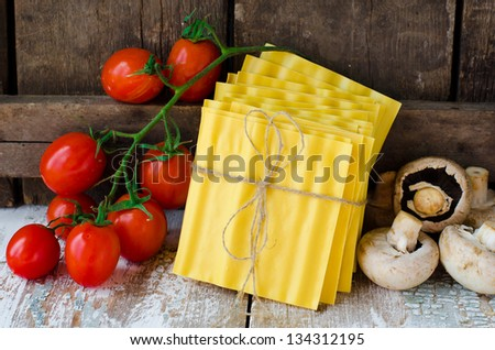 The leaves of lasagna , fresh tomatoes, mushrooms and herbs.	 Selective focus - stock photo