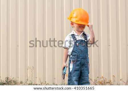 The Little boy in the helmet of the builder.