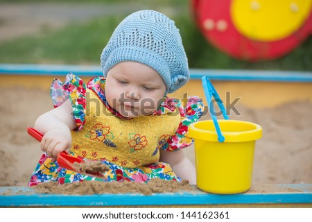 The little girl plays to a sandbox - stock photo