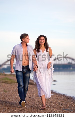 The man and the woman go on coast - stock photo
