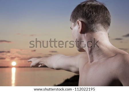 The man shows a finger on the sun - stock photo