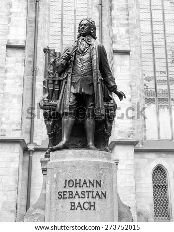 The Neues Bach Denkmal meaning new Bach monument stands since 1908 in front of the St Thomas Kirche church where Johann Sebastian Bach is buried in Leipzig Germany in black and white - stock photo