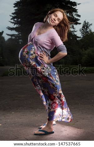 The pregnant woman costs in park - stock photo
