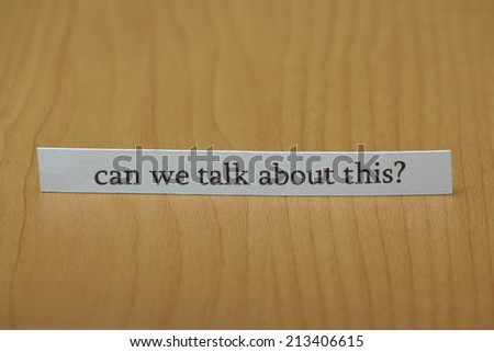 The question can we talk about this typed on a strip of paper left standing on a wooden desktop
