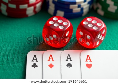 the red casino dice and poker cards on green table - stock photo